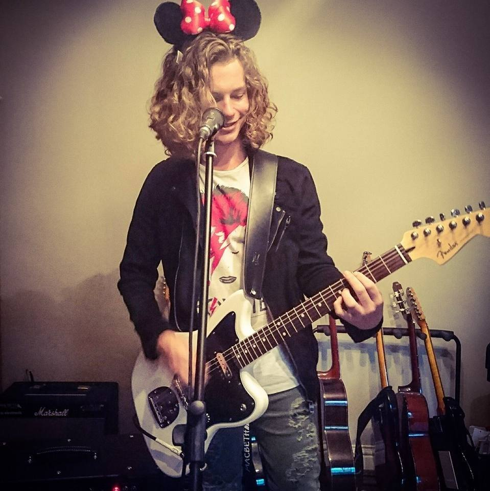 Rupert playing guitar wearing Minnie Mouse ears